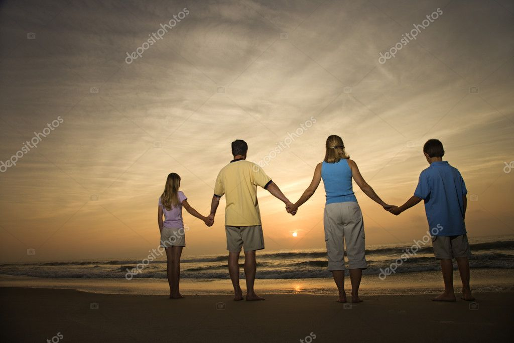 Family of four holding hands on beach watching the sunset. Horizontally framed shot. — Stock Photo #9498353