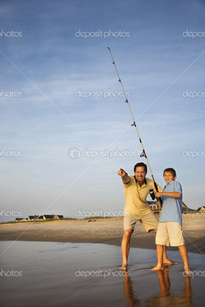 Caucasian mid-adult man shore fishing on beach with pre-teen boy and pointing.  Stock Photo #9498365