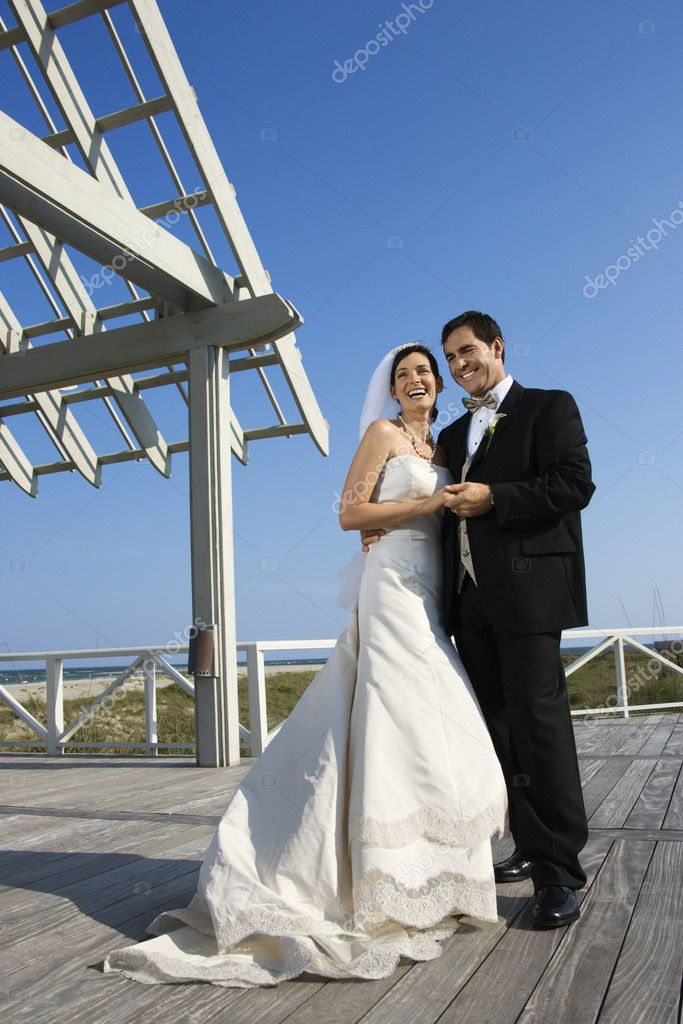 Caucasian mid-adult bride and groom wedding portrait outside at beach.  Stock Photo #9499099