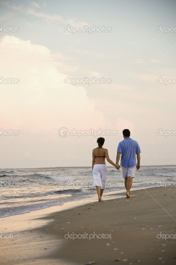 Rear view of a couple walking on the beach, holding hands. Vertical shot. — Stock Photo #9499173