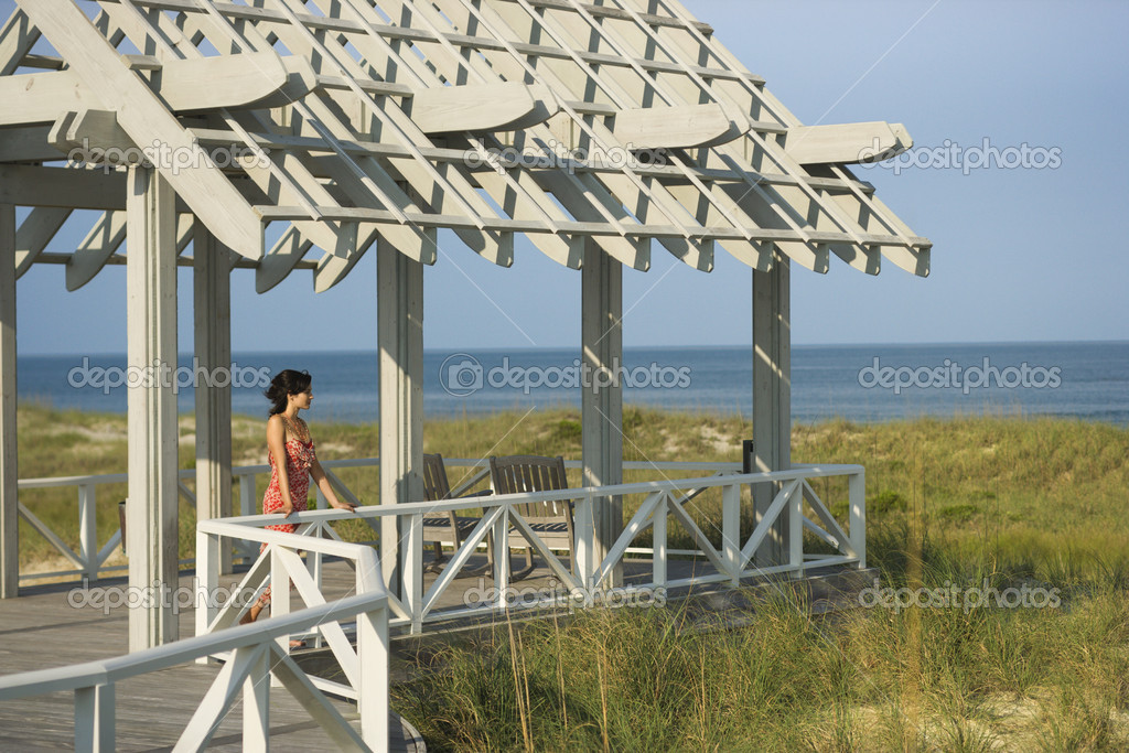 Woman leans on an arbor railing looking out at the ocean. Horizontal shot. — Stock Photo #9499257