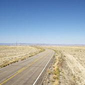Road through barren landscape. — Stock Photo