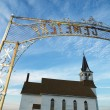 Cemetary entry with church. — Stock Photo