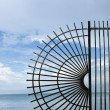Wrought iron fence by ocean. - Stock Photo