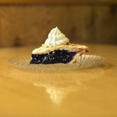 Slice of blueberry pie on plate with whipped topping. — Stock Photo