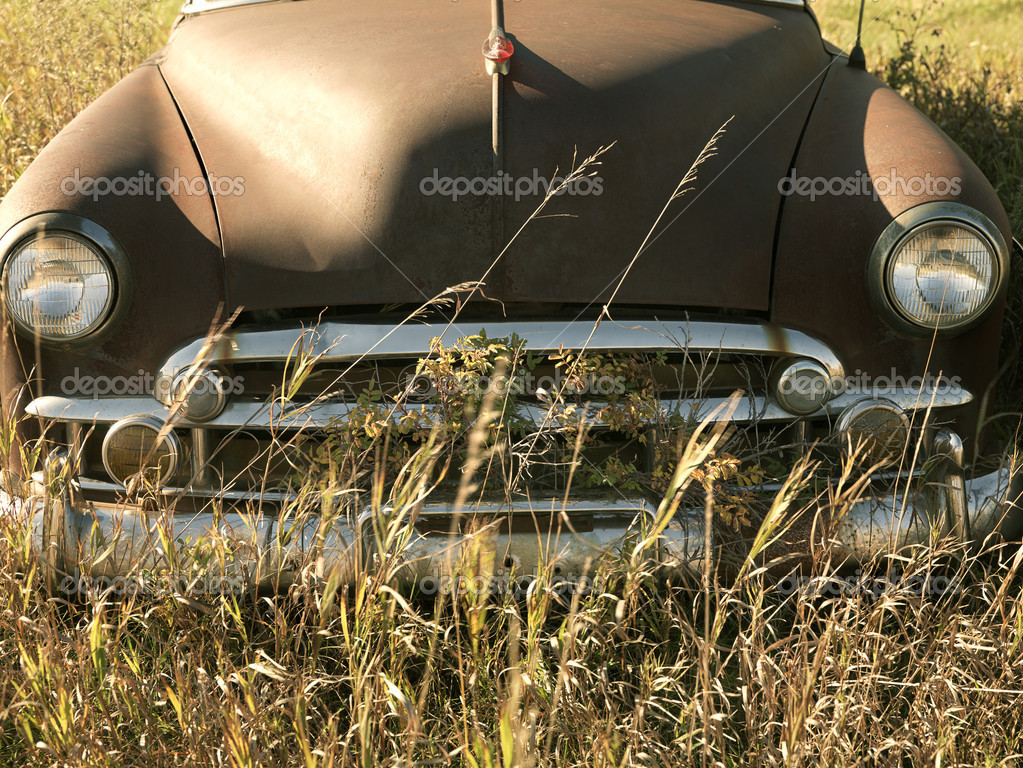 Front end of old abandoned antique car in field.  Stock Photo #9513394