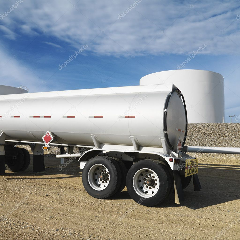 Side view of fuel tanker truck with fuel tank farm in background.  Stock Photo #9513455