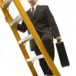 Businessman climbing ladder. - Stock Photo