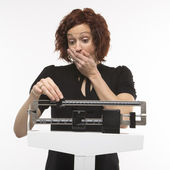 Woman weighing self. — Stock Photo