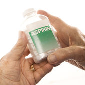 Hands holding aspirin bottle. — Stock Photo