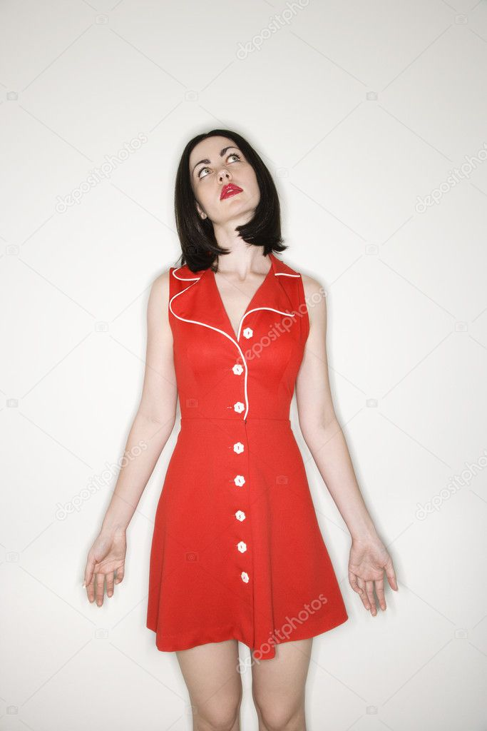 Caucasian young adult woman wearing red retro dress looking upwards. — Stock Photo #9521665