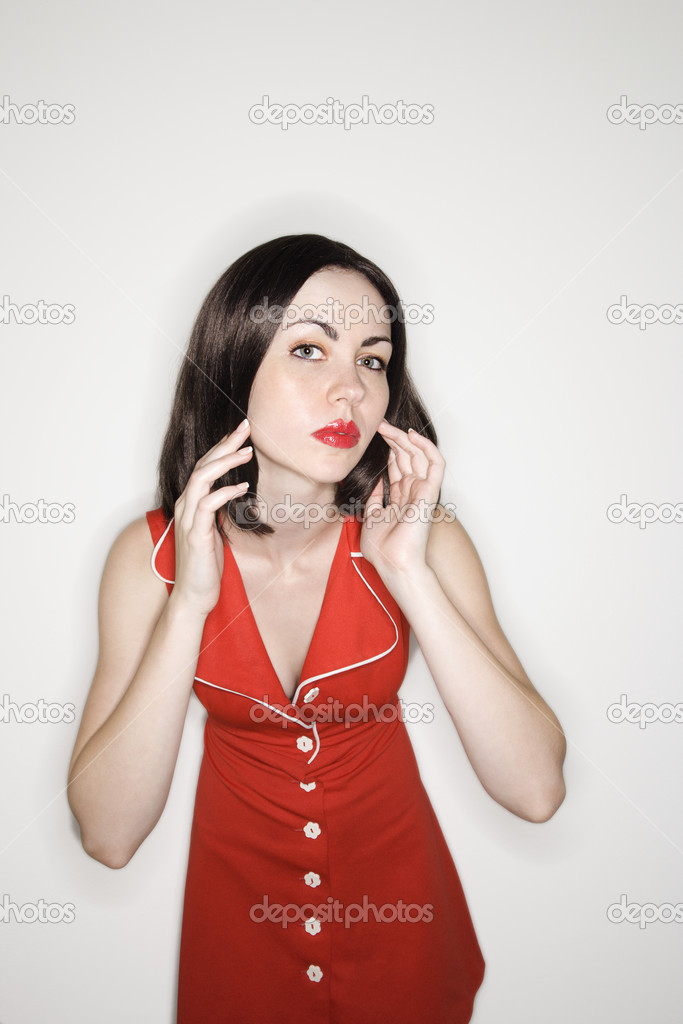 Caucasian young adult woman in retro dress looking at viewer with hands on face. — Stock Photo #9521666
