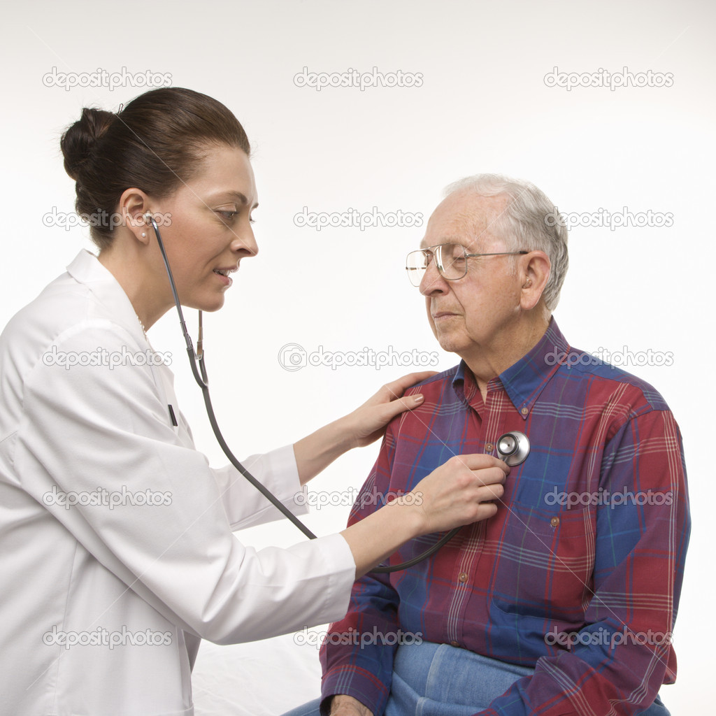 Mid-adult Caucasian female doctor listening  to elderly Caucasian male's heartbeat with stethoscope. — Stock Photo #9523582
