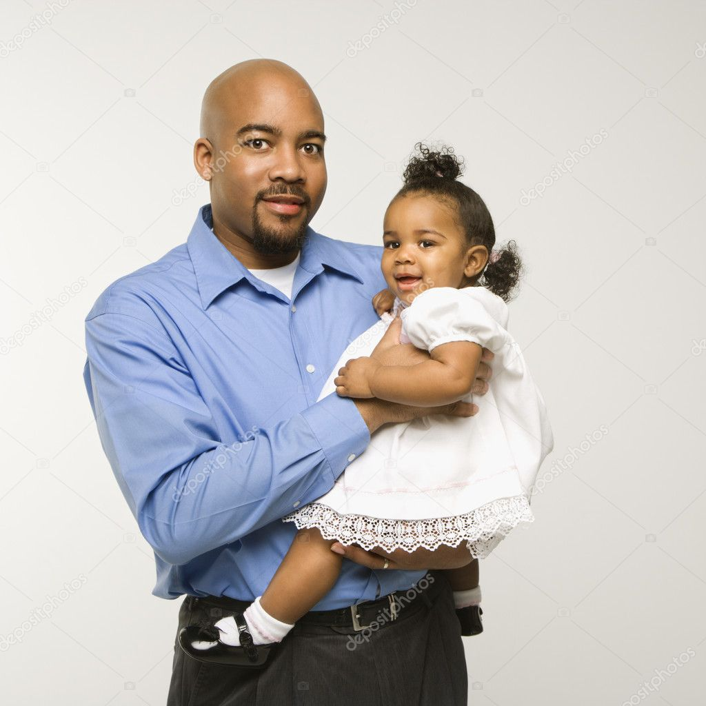 African American man holding infant girl standing against white background.  Stock Photo #9523680
