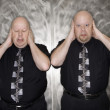 Stock Photo: Twin men covering ears.