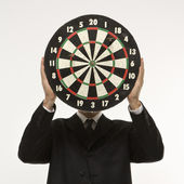 Dartboard in front of face. — Stock Photo