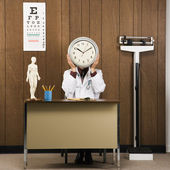 Doctor holding clock. — Stock Photo