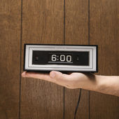 Hand holding alarm clock. — Photo