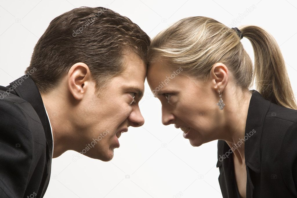Caucasian mid-adult man and woman with foreheads together staring at each other with hostile expressions.  Stock Photo #9530306