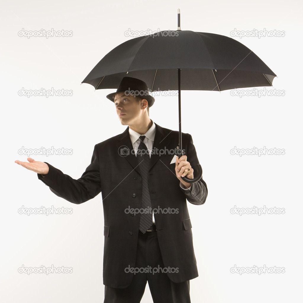 Caucasian mid-adult businessman wearing fedora holding umbrella with arm outstretched. — Stock Photo #9530326