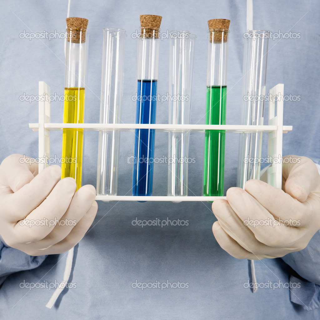 Close-up of male surgeon's hands holding test tube tray.  Stock Photo #9530539