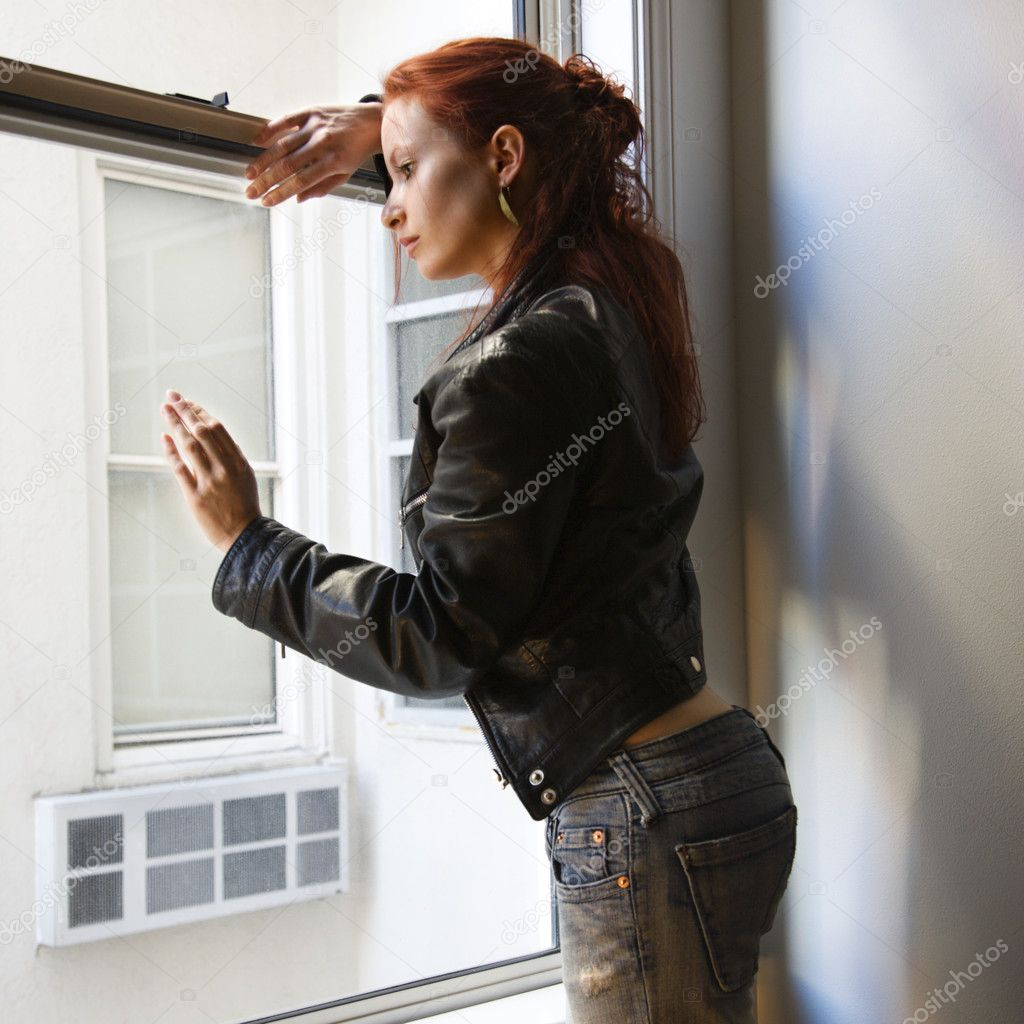 Pretty redhead young woman standing indoors leaning against window looking outside. — Stock Photo #9531628