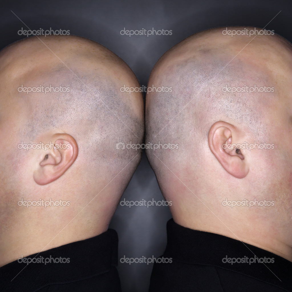 Close up of Caucasian mid adult identical twin bald men standing back to back. — Stock Photo #9531900