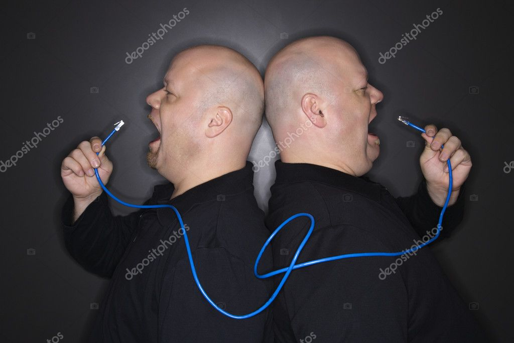 Caucasian bald mid adult identical twin men standing back to back yelling into ethernet cable. — Stock Photo #9531911