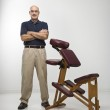Massage therapist and chair. — Stock Photo