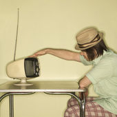 Man tapping retro TV. — Stock Photo