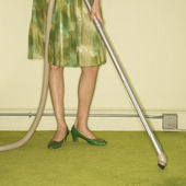 Woman vacuuming rug. — Stock Photo