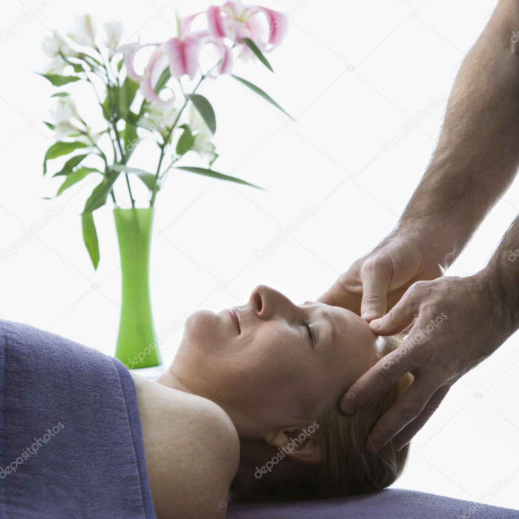 Caucasian middle-aged male massage therapist massaging temples of Caucasian middle-aged woman lying on massage table. — Stock Photo #9547804