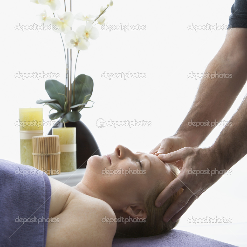 Caucasian middle-aged male massage therapist massaging temples of Caucasian middle-aged woman lying on massage table. — Stock Photo #9547806