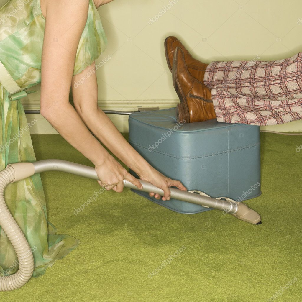 Caucasian mid-adult woman kneeling and vaccuuming carpet around male feet resting on foot stool. — Stock Photo #9549155