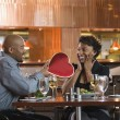 Man Giving Woman Heart Shaped Box at Restaurant — Stock Photo