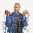 Man wrapped in cables. - Stock Photo