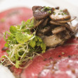 Beef carpaccio with mushrooms. - Stock Photo