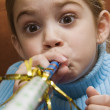 Stock Photo: Girl blowing noisemaker.