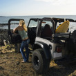 Woman with SUV at the Beach - Stockfoto