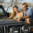 Couple With Map on Car Hood — Stock Photo