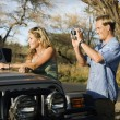 Tourist Couple Standing By Car - Stock Photo