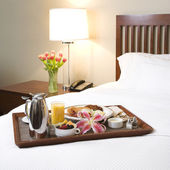 Breakfast tray on white bed. — Stock Photo