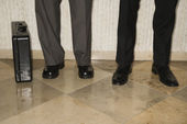 Two male's legs and briefcase. — Stock Photo
