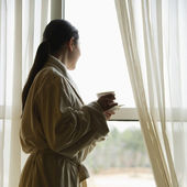 Woman looking out window. — Stock Photo