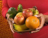 Hands holding fruit basket. — Stock Photo