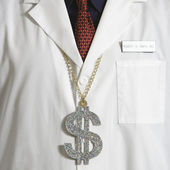 Doctor wearing dollar sign. — Stock Photo
