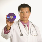 Doctor holding compact disc. — Stock Photo
