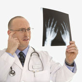 Doctor looking at xrays. — Stock Photo