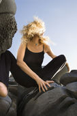Woman crouching on rocks. — Stock Photo