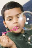 Boy blowing bubbles. — Stock Photo